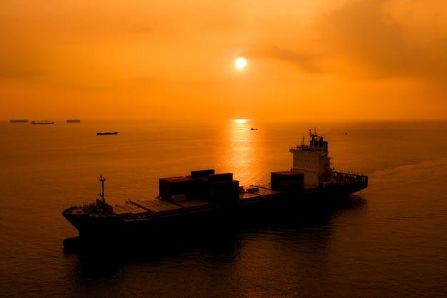 Kontenery do przewozu ładunków sylwetka import eksport międzynarodowy na morzu wieczorem