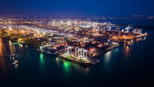 Kontenery magazynowe terminali portów morskich i kontenery transportowe załadunek i rozładunek w nocy widok z lotu ptaka