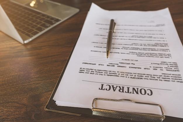 Kontraktuje papiery i pióro z laptopem na drewnianym biurku