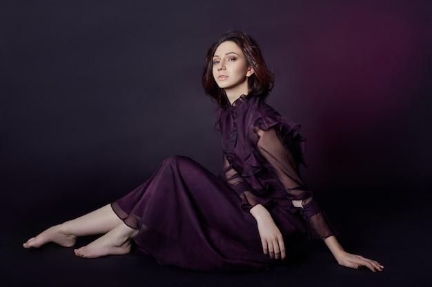 Kontrast moda ormiański portret kobiety z dużymi niebieskimi oczami siedzi na ciemnym tle w fioletowej sukience. urocza wspaniała dziewczyna pozuje w sukni wieczorowej. jasny makijaż, kobieto