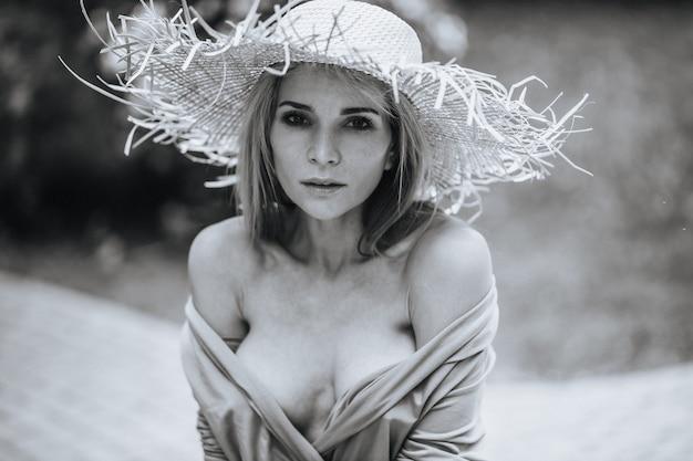 Kontrastowy czarno-biały portret seksownej czarującej dziewczyny w kapeluszu i sukience w naturze