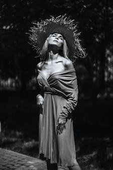 Kontrastowy czarno-biały portret seksownej czarującej dziewczyny w kapeluszu i sukience w przyrodzie. z ziarnem filmu, hałasem