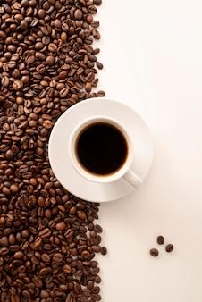 Kontrastujący kawowych fasoli tło i filiżanka