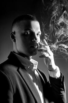 Kontrastuje portret palacza biznesmena w drogim garniturze na ciemnym tle. pomyślny emocjonalny kierownika biznesmen pozuje gestykuluje ręki i dymi papieros na czerni