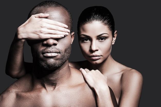 Kontrasty. piękna kobieta rasy kaukaskiej, która przywiązuje się do przystojnego afrykanina i zakrywa mu oczy dłonią, gdy oboje stoją na szarym tle