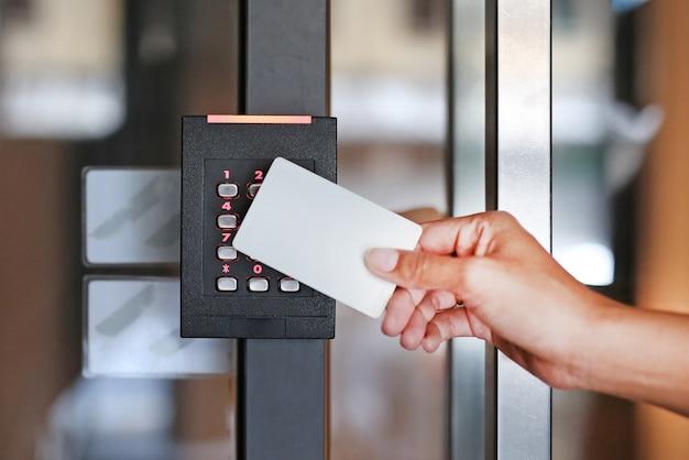 Kontrola dostępu do drzwi - młoda kobieta trzyma kluczową kartę do blokowania i odblokowywania drzwi.