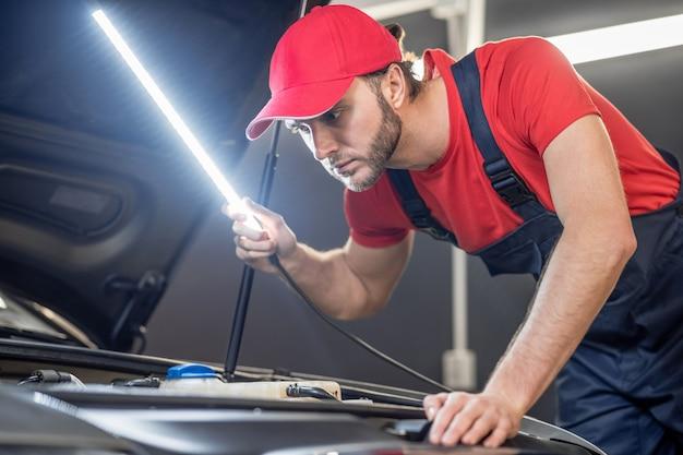 Kontrola. doświadczony, młody dorosły mechanik w czapce i kombinezonie z lampką sprawdzający anatomię samochodu w warsztacie