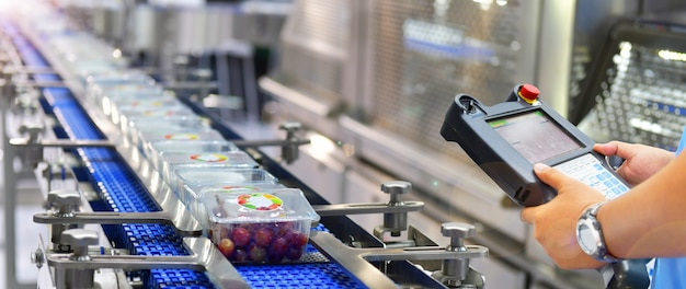 Kontrola menedżera i automatyzacja kontroli przenoszenie pudeł produktów spożywczych na zautomatyzowane systemy przenośników w fabryce