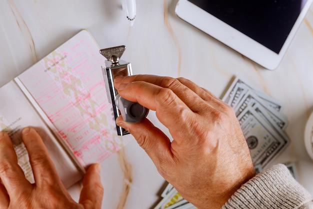 Kontrola paszportowa imigracyjna u funkcjonariusza kontroli granicznej lotniska umieszcza pieczęć w paszporcie.