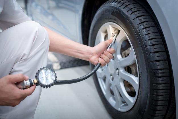 Kontrola samochodu azjatyckiego człowieka zmierz ilość napompowane gumowe opony samochodowe