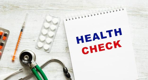 Kontrola zdrowia jest zapisana w zeszycie na białym stole obok tabletek i stetoskopu. pojęcie medyczne