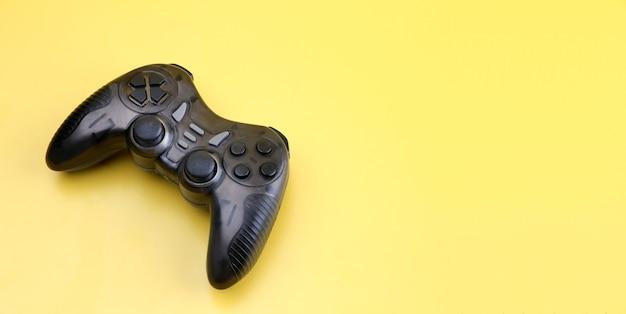Kontroler do gier joystick na żółtym tle.