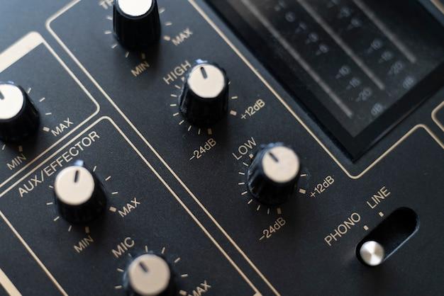 Kontroler miksera dźwięku z bliska z regulowanymi pokrętłami i suwakami