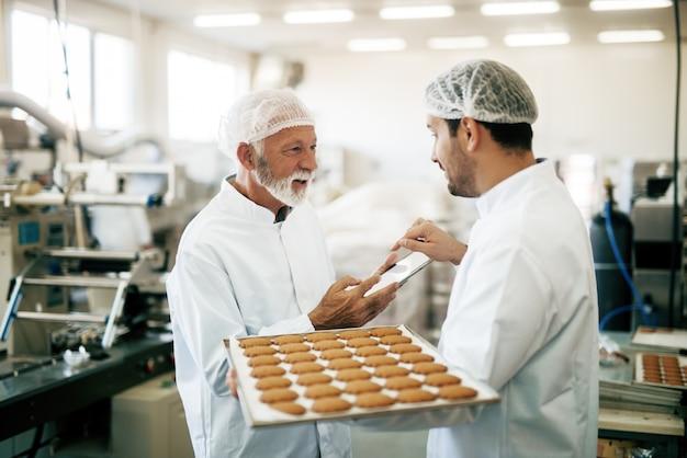 Kontroler rozmawia z pracownikiem podczas korzystania z tabletu. pracownik niosący talerz z ciasteczkami. ubranie ochronne. wnętrze fabryki żywności.