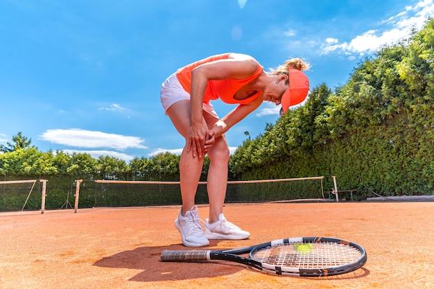 Kontuzja kolana na korcie tenisowym, młoda kobieta gracz.