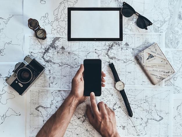 Kontynuuj podróż. widok z góry na człowieka za pomocą smartfona z okularami przeciwsłonecznymi, aparatem fotograficznym, kompasem