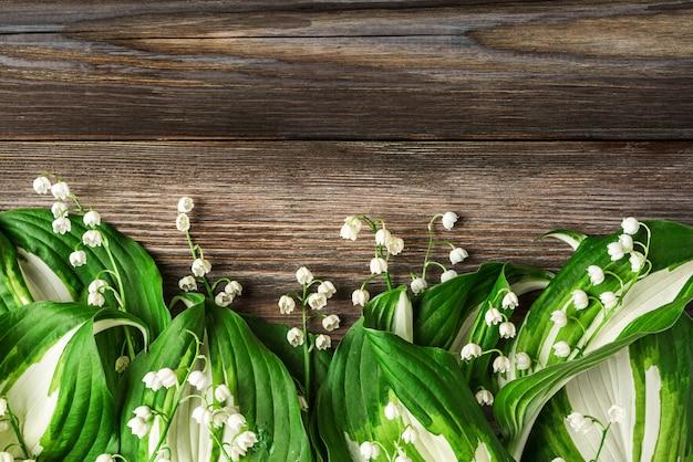 Konwalia kwiaty na rustykalnym drewnianym. widok z góry z miejscem na kopię