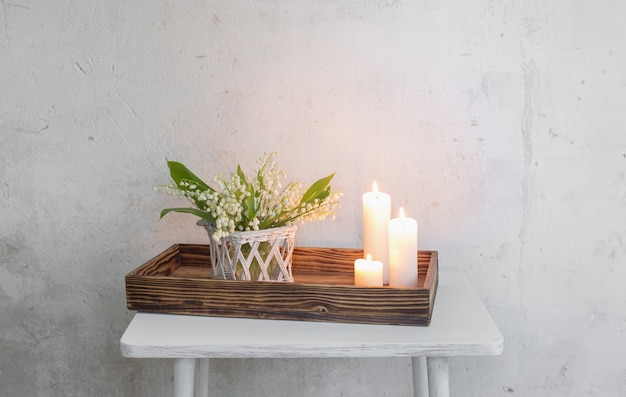 Konwalia w wazonie z płonącymi świecami na powierzchni starej białej ściany