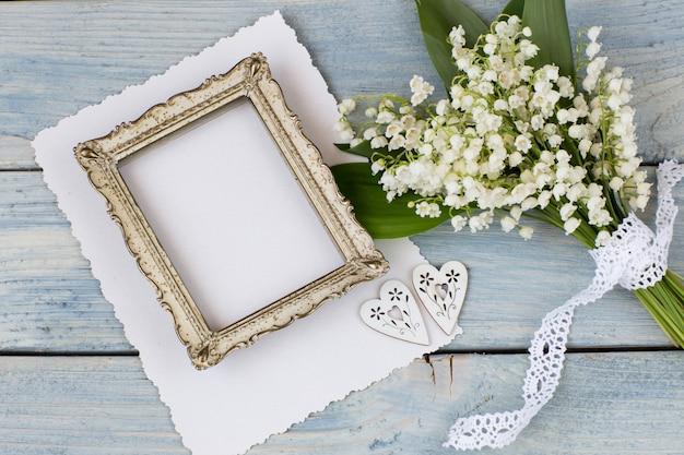 Konwalie na niebieskim tle drewniane, stara ramka na zdjęcia, arkusz papieru dwa serca