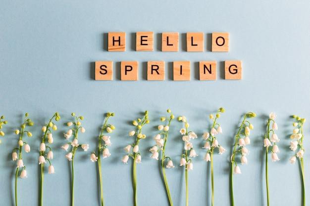 """Konwalie na niebieskim zdjęciu i napis drewnianymi literami """"witaj wiosno""""."""