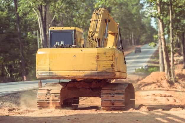 Koparka koparka wylewa ziemię na drodze.