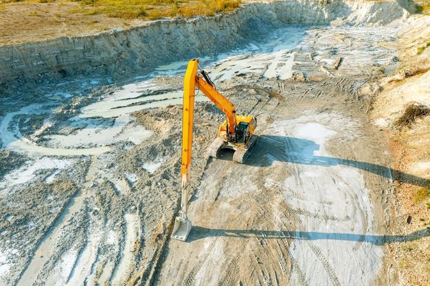 Koparka na placu budowy planuje grunt przed pracami przy fundamentach