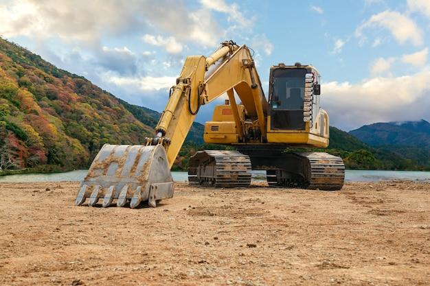 Koparka na ziemię. plac budowy przy lagunie, koparka, ładowarka kołowa.