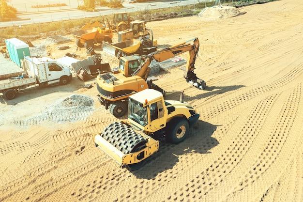 Koparka oczyszcza plac budowy poprzez ubijanie ziemi specjalnym ubijakiem.