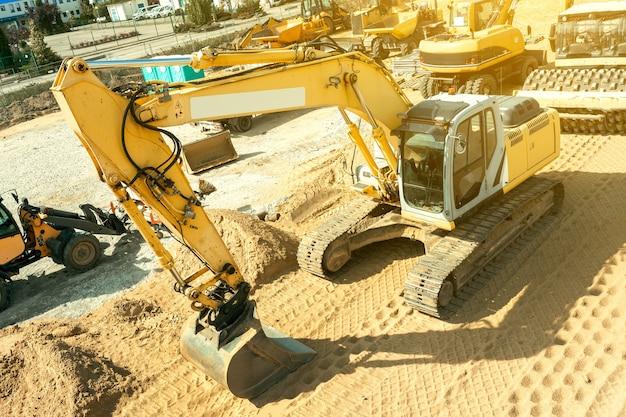 Koparka planuje teren na placu budowy, koparka kopie rowy
