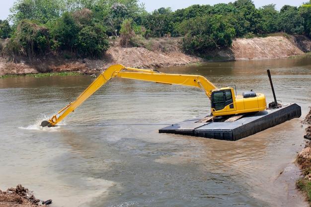 Koparka pracuje na rzece w celu ochrony przed powodzią