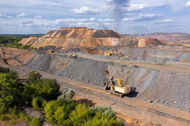 Koparka stoi na tle sprzętu górniczego w zakładzie górniczym.