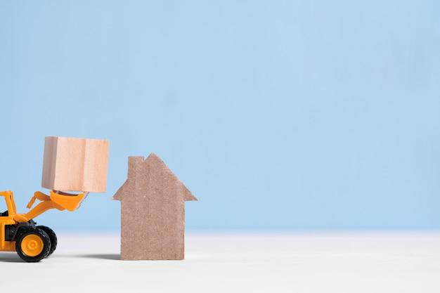 Koparka z zabawkami dostarcza drewniany sześcian do kartonowego domu z wycinanką z copyspace.