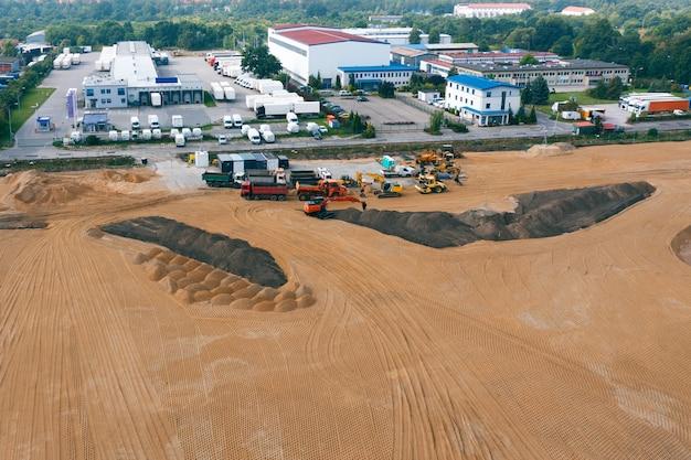 Koparki i inny sprzęt budowlany pracujący na budowie, widok z góry
