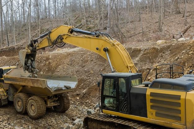 Koparki współpracują z traktorem do przewozu kamienia, który ładuje ciężarówki do transportu kamienia