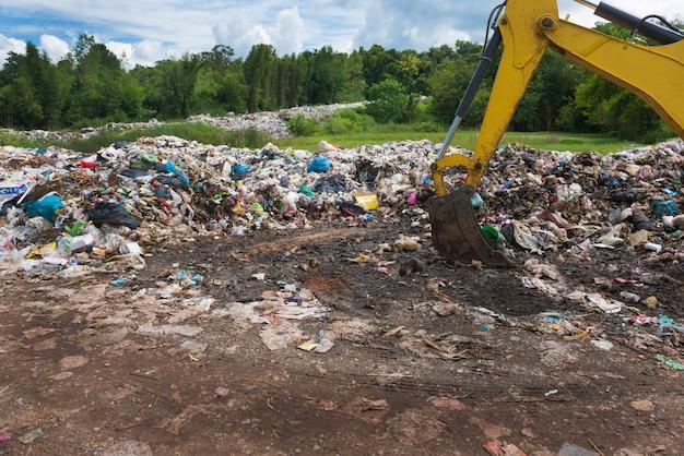 Koparko-ładowarka pracuje na wysypisku śmieci