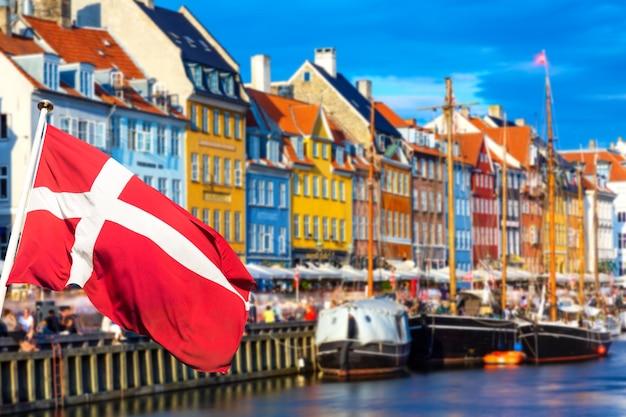 Kopenhaga kultowy widok. słynny stary port nyhavn w centrum kopenhagi w letni słoneczny dzień z flagą danii na pierwszym planie.