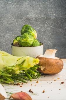 Koper włoski; grzyby i brukselka na drewnianym stole