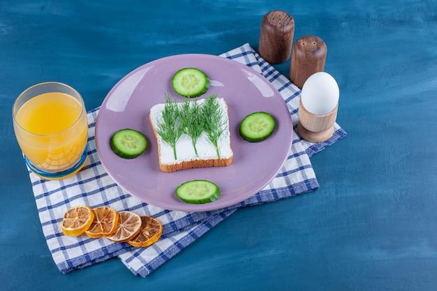 Koperek na chlebie serowym obok pokrojonego ogórka na talerzu obok materiałów na ściereczce na niebiesko.