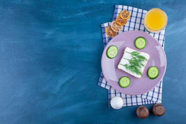 Koperek na pieczywie serowym obok pokrojonego ogórka na talerzu obok materiałów na ściereczce, na niebiesko.