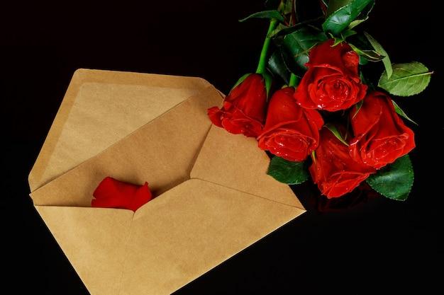 Koperta i bukiet czerwonych róż na czarnym stole. koncepcja walentynki.
