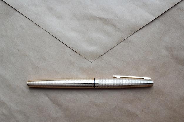 Koperta i złoty długopis na stole