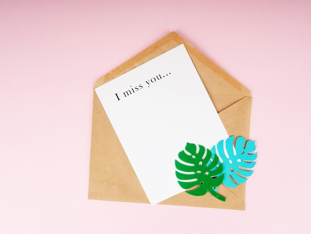"""Koperta kraft i biała kartka papieru, na górze liście z papieru monstera i napis """"tęsknię za tobą"""""""