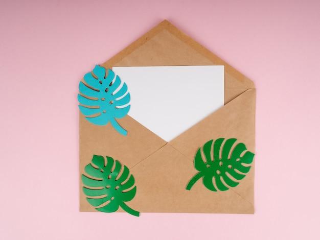 Koperta kraft i biała kartka papieru, z listkami z papieru monstera u góry.