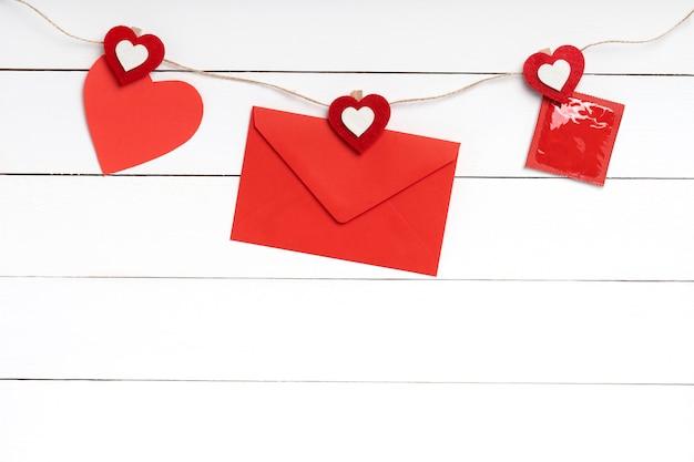 Koperta, list, czerwone serce valentine i prezerwatywa wiszące na linie za białą drewnianą powierzchnią. skopiuj miejsce, widok z góry.