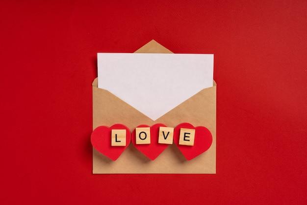 Koperta papierowa z białą kartką tekstu na czerwonym tle z sercami