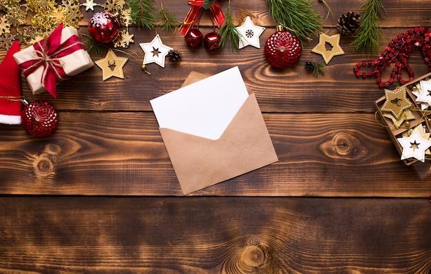 Koperta pocztowa wykonana z papieru kraftowego z białą kartką na tekst na drewnianym tle ze świątecznymi dekoracjami. list do świętego mikołaja, lista życzeń, marzenie noworoczne, prezent. leżał płasko, kopia przestrzeń