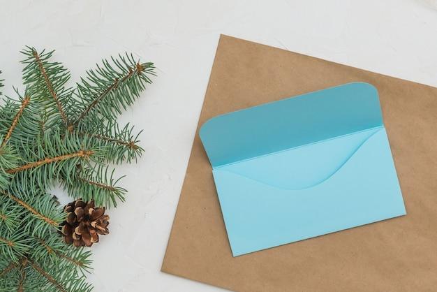 Koperta prezentowa wykonana z papieru kraftowego na tle jodły list oraz koperta ręcznie robiona na boże narodzenie.