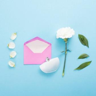 Koperta z białym kwiatem na błękita stole
