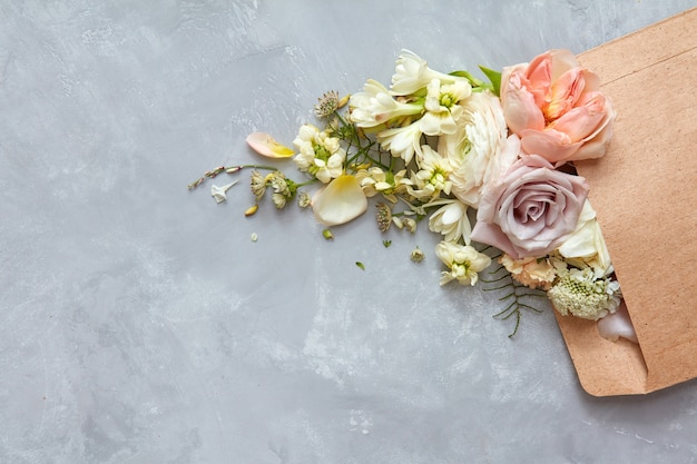 Koperta z kwiatami na kamiennym szarym tle. mieszkanie leżało
