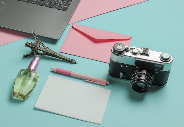 Koperta z listem, aparatem retro, laptopem i akcesoriami kosmetycznymi na różowym niebieskim tle pastelowych. widok z góry. koncepcja podróży.